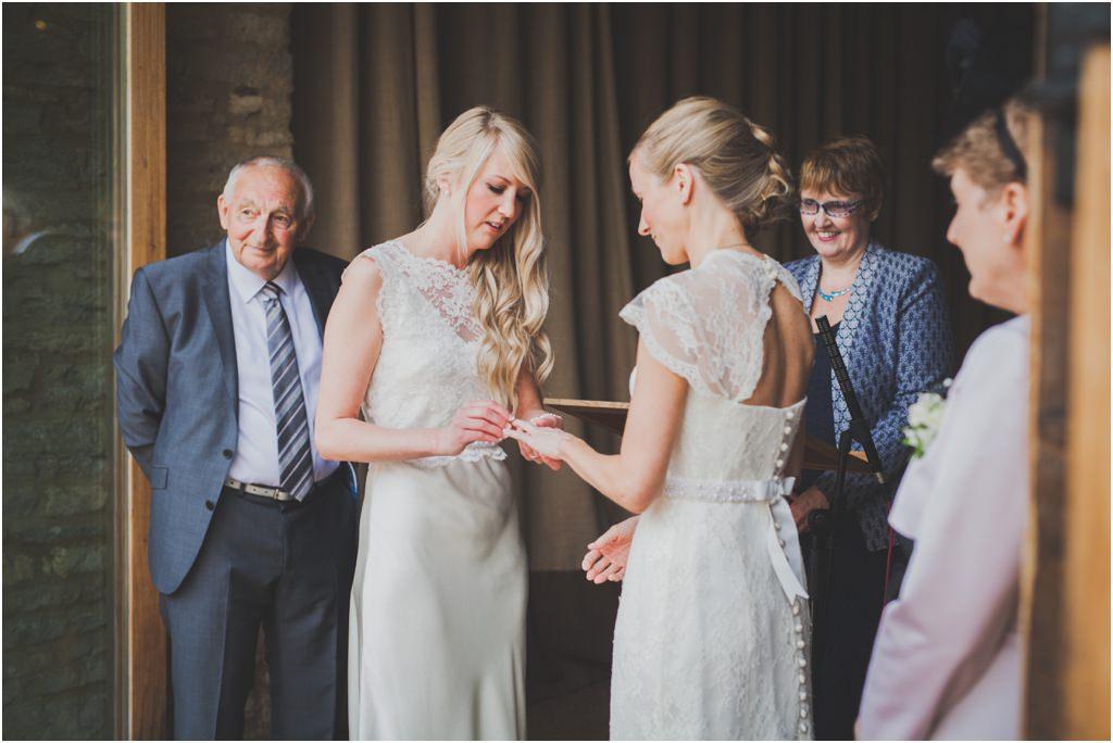 Two brides exchanging wedding rings at same sex wedding - photo on Gay Wedding Blog