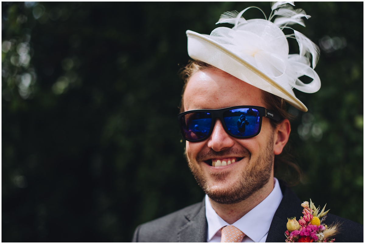 Image of a man in a female hat taken by a wedding photographer Eames Photography