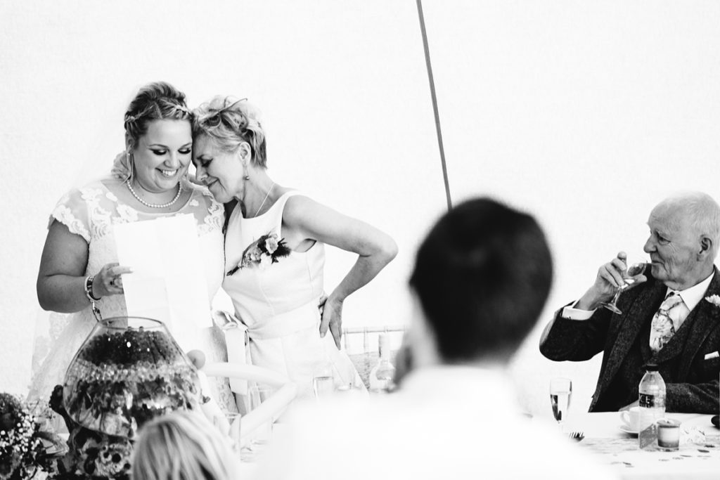 Black and white picture of two brides giving a speech at a wedding - Gay Wedding Blog