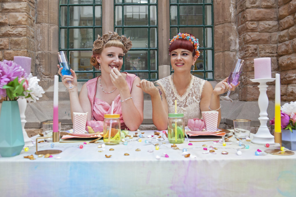 Wedding Event poster - two brides sitting at a table - Gay Wedding Blog