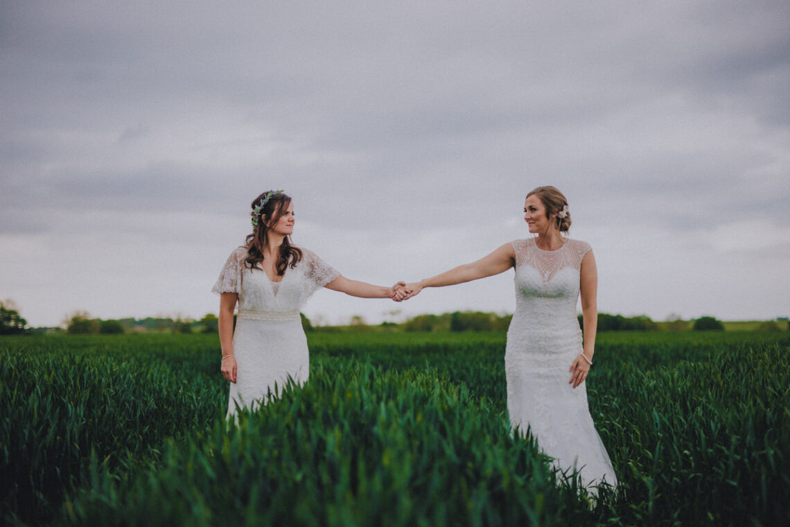 Gay Wedding Blog - Scottish wedding - two brides holding hands in the field